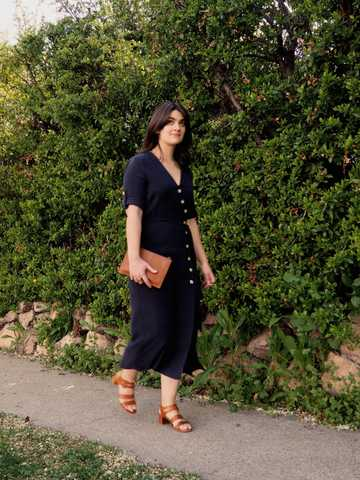 Sara wearing navy blue midi dress with tortoise shell buttons down front