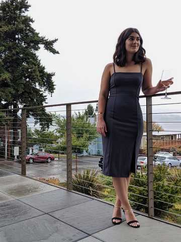 Sara standing by a railing wearing gray, knee-length spaghetti strap dress