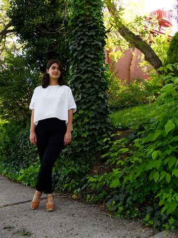 Sara wearing white cotton top and black high waist trousers with natural leather clogs