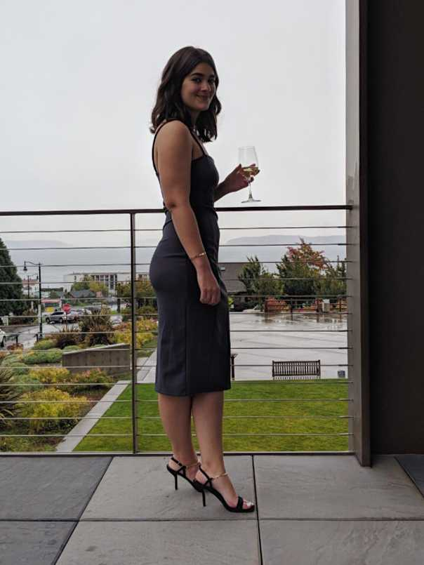 Profile of Sara in gray sheath dress and black sandals with gold chain ankle strap